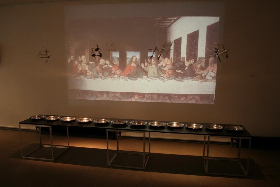 А. Колейчук. Тарелки для двенадцати… Инсталляция, 2004. Нержавейка, гравировка, свет.